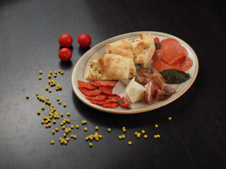 Snack on a plate with cheese, salami, bacon and pita bread on a dark table