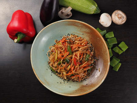 Plate of noodles with meat and vegetables on dark table, top view