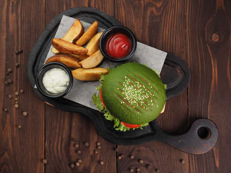 Perfect meat burger with fried potatoes on the background of a wooden table