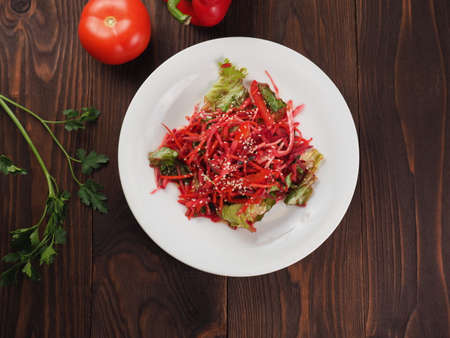 Salad of red and white cabbage and sweet red pepper, seasoned with lemon juice and olive oil in a white plate on a wooden table