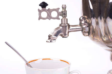 Closeup of traditional russian tea kettle faucet and teacup photo
