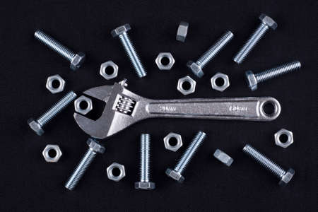 Adjustable wrench with screws and nuts on black background photo