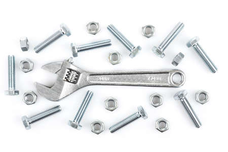 Adjustable wrench with screws and nuts on white background photo