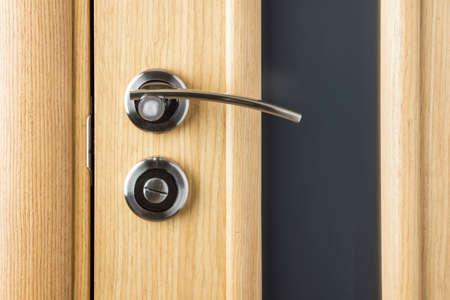 hotel room door: Handle on wooden and glass door close up Stock Photo