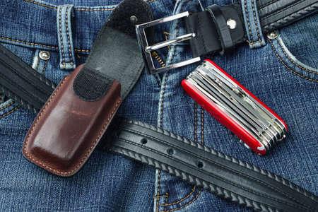 temperino: Dettaglio di blu jeans con cintura di pelle, temperino e caso Archivio Fotografico