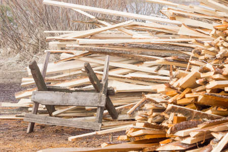 sawhorse: Sawbuck on pile of firewood background Stock Photo