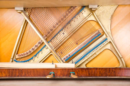 pedals: Bottom structure of an upright piano: pedals, metal frame with strings, bass and treble bridges. Stock Photo