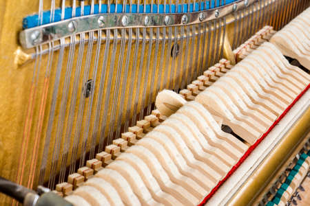 Pattern of hammers and strings inside piano, close up. One hummer in action while key is pressed. Stand out from the crowd concept.