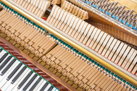 upright piano: Action mechanics close up inside of an upright piano. Pattern of keys, shanks, hammers and strings.