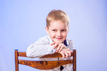 Portrait of cute smiling boy posing on chair