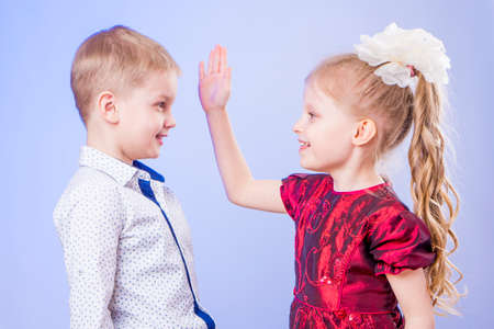 Portrait of little boy and girl having fun on blue background