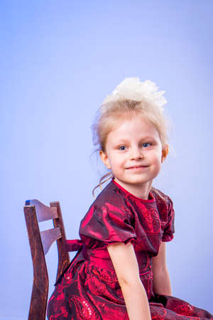 Portrait of little girl in dark red dress sitting sideways on chair on blue background