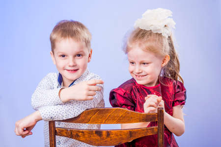Portrait of smiling little boy and girl having fun and sitting on chair Standard-Bild