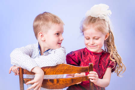 Portrait of little boy and girl talking and sitting on chair Standard-Bild