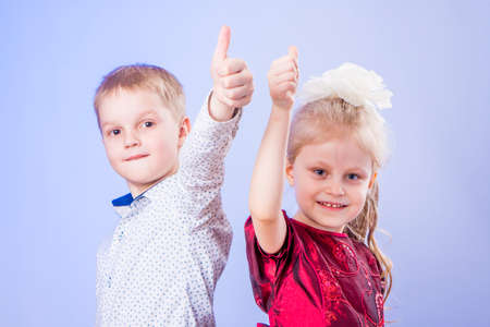 Portrait of little boy and girl with thimbs up on blue background