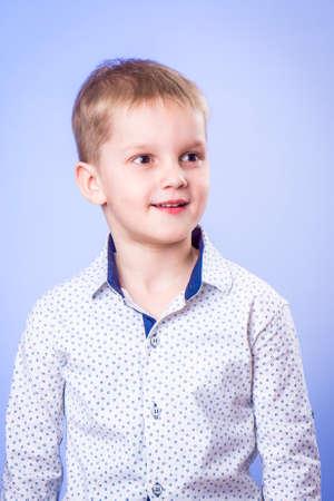 Portrait of cute little boy on blue background Standard-Bild