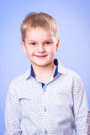 Portrait of smiling little boy on blue background Zdjęcie Seryjne