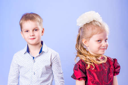 Portrait of funny little boy and girl on blue background