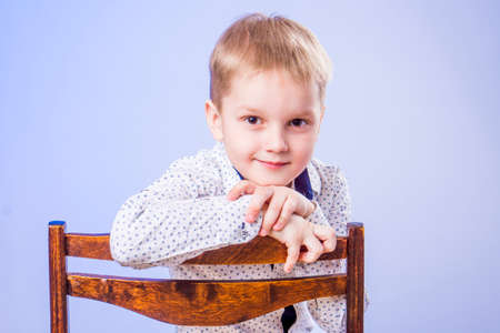 Portrait of cute little boy posing on chair Zdjęcie Seryjne