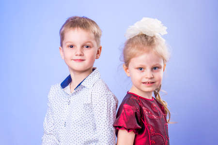 Portrait of little boy and girl on blue background