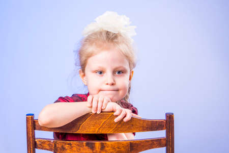 Portrait of dreaming little girl sitting on chair