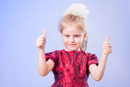 Little girl in dark red dress showing two thumbs up