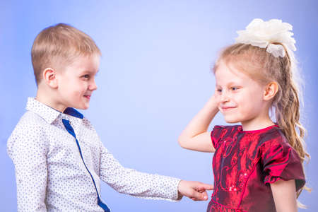Portrait of little boy and girl smiling and having fun on blue background