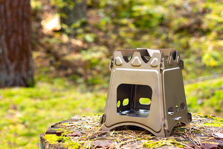Folding wood stove designed for cooking outdoors using twigs as fuel on nature background Stock fotó
