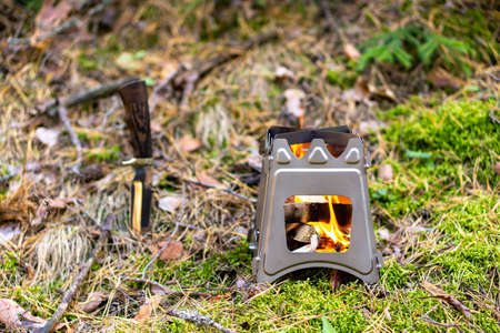 Burning foldable wood stove designed for cooking outdoors using twigs as fuel on nature background Zdjęcie Seryjne