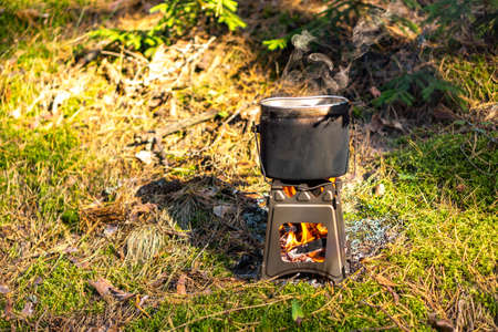Pot boiling on wood burning twig stove outdoors