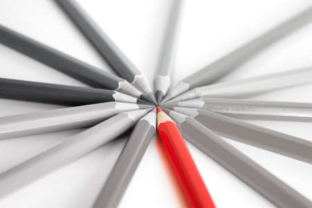 thinking out of the box: Bright red pencil standing out among gray pencils, concept of thinking differently and out of the box. On a white background with soft focus.