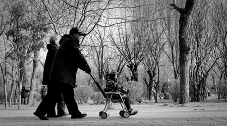 old couple walking: Old couple walking in the park with kid in the stroller