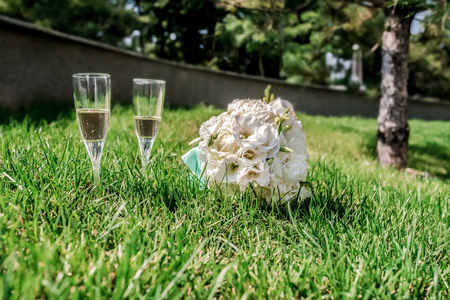 bocal: a bridal bouquet and couple bocal of shampagne at green grass Stock Photo