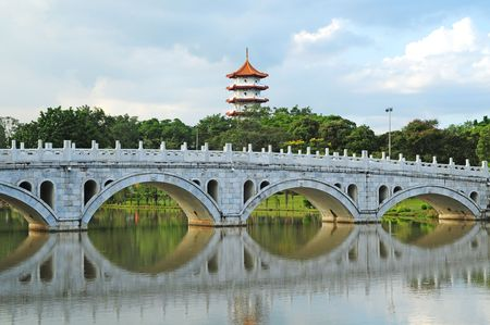 Chinese Styled Bridge With Pagoda In The Background photo