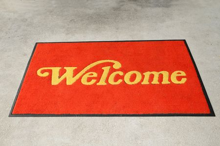 Red Welcome Mat  Outside A Restaurant Stock Photo