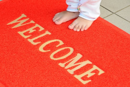 welcome home: Child standing On A Welcome Mat Stock Photo