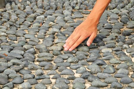 Hand Touching The Cobblestone Of A Walkway photo