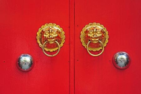 Lion Heads Door Handle On Red Doors photo