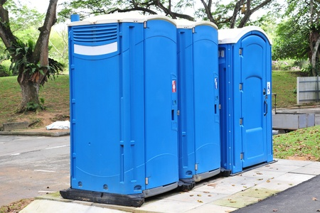 Three Blue Portable Toilets In The Park Stock Photo