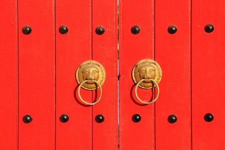Lion Head Door Handle On Red Doors photo
