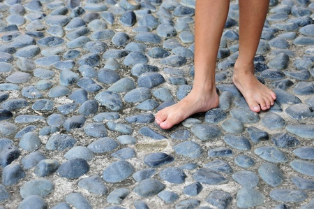 Walking Bare-Footed On Cobblestone Pavement photo