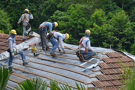 refurbish: Workers Doing Installation Work On The Roof Of A Building
