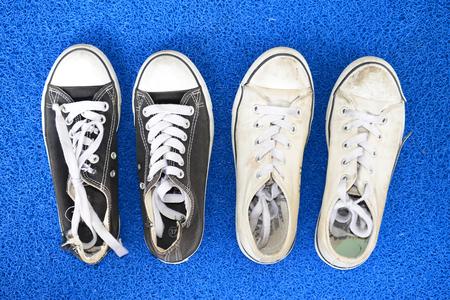 floor mat: Worn Canvas Shoes On A Blue Floor Mat