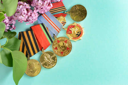 Medals after the Second World War in lilac flowers closeup on light blue background