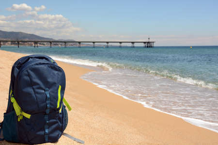 packsack: Travel concept. Sports backpack on the seashore on the background of the pier and mountains