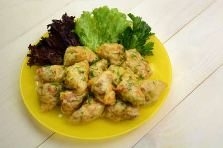 Cabbage rolls stuffed with chicken meat ri e and vegetables on white wooden table. Asian food closeup