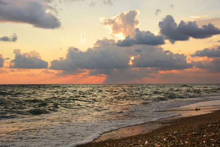 Sunset at sea. Cumulus clouds and rays of the setting sun