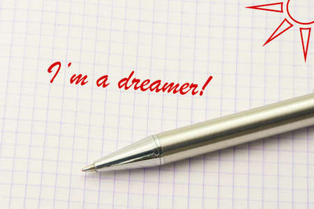 Dreamer word written on paper. Dreaming textual concept with sun and silver pen closeup