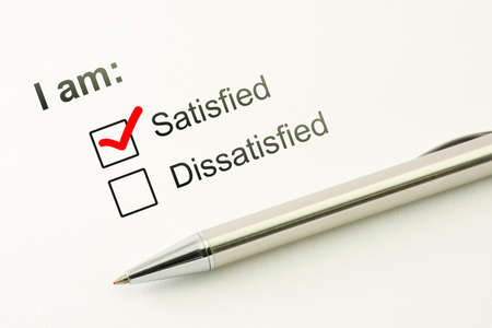 Satisfied choice concept. Consumer satisfaction feed back. Customer service evaluation. Marked checkbox dissatisfied options with a silver pen on paper background