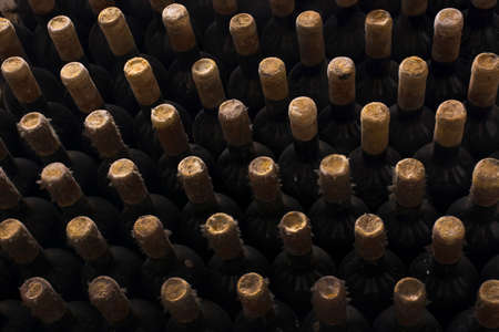 Wine bottles stacked up in old wine cellar background. Tasty aging drink in dusty bottles